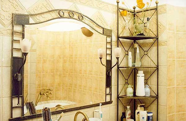 Зеркало в кованой отделке увеличивает пространство санузла