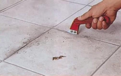 Чтобы не повредить соседние плитки, удаляем затирку из швов