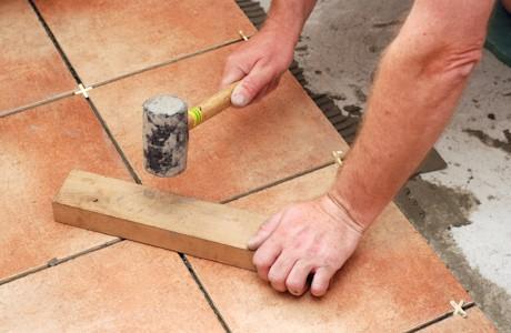 Выравнивание плитки с помощью резинового молотка и деревянного бруска