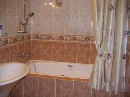 Ванная и ванна, отделанная кафельной плиткой