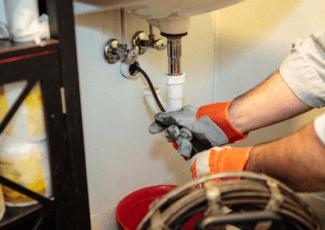 На фото - прочистка канализационной трубы тросом