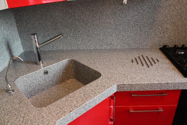 Возле раковины в столешницу вплавлена металлическая подставка для горячей посуды. Она нужна именно для того, чтобы избежать термических повреждений поверхности.