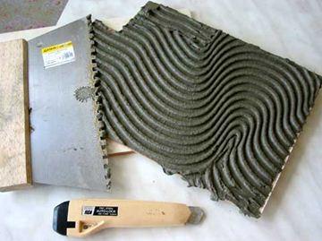 Нанесение клеящего раствора на поверхность плитки увеличивает сцепление ее с основанием и в некотором роде отвечает на вопрос, как поклеить кафельную плитку.