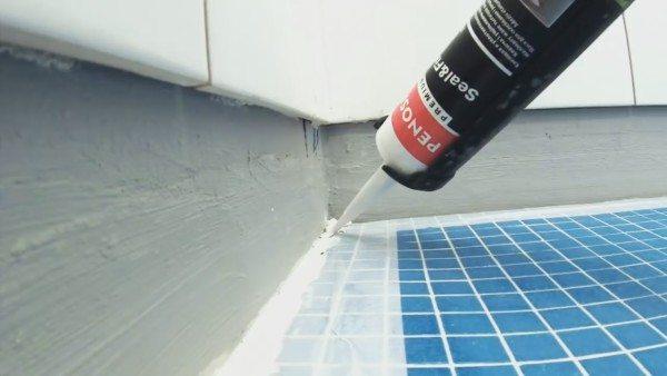 Нанесение силиконового герметика на стыке стен и пола