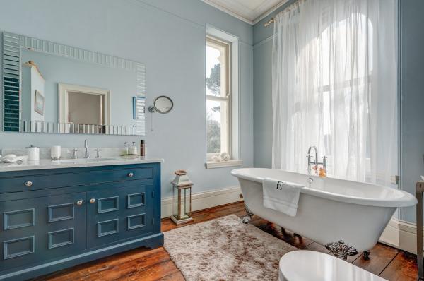 Особое внимание стоит уделить сантехнике и мебели. Ванна на роскошных ножках, миниатюрные комоды в пастельном цвете, легкий голубой оттенок для стен повышают настроение и добавляют нежности
