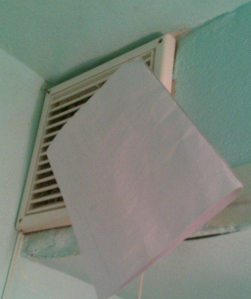 Притянутый к вентиляционной решётке бумажный лист