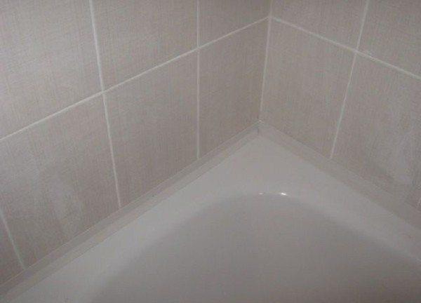 Заделанный бордюрной лентой стык ванны и стены